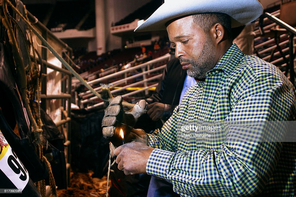 Steven Gabriel of Houston Texas burns a glove with a sticky rosin upon it to prevent him from coming loose from his saddle during his bronco horse...