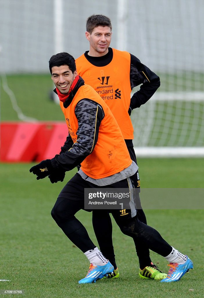 Steven Gerarrd and Luis Suarez of Liverpool share a joke during a training session at Melwood Training Ground on February 21, 2014 in Liverpool, England.