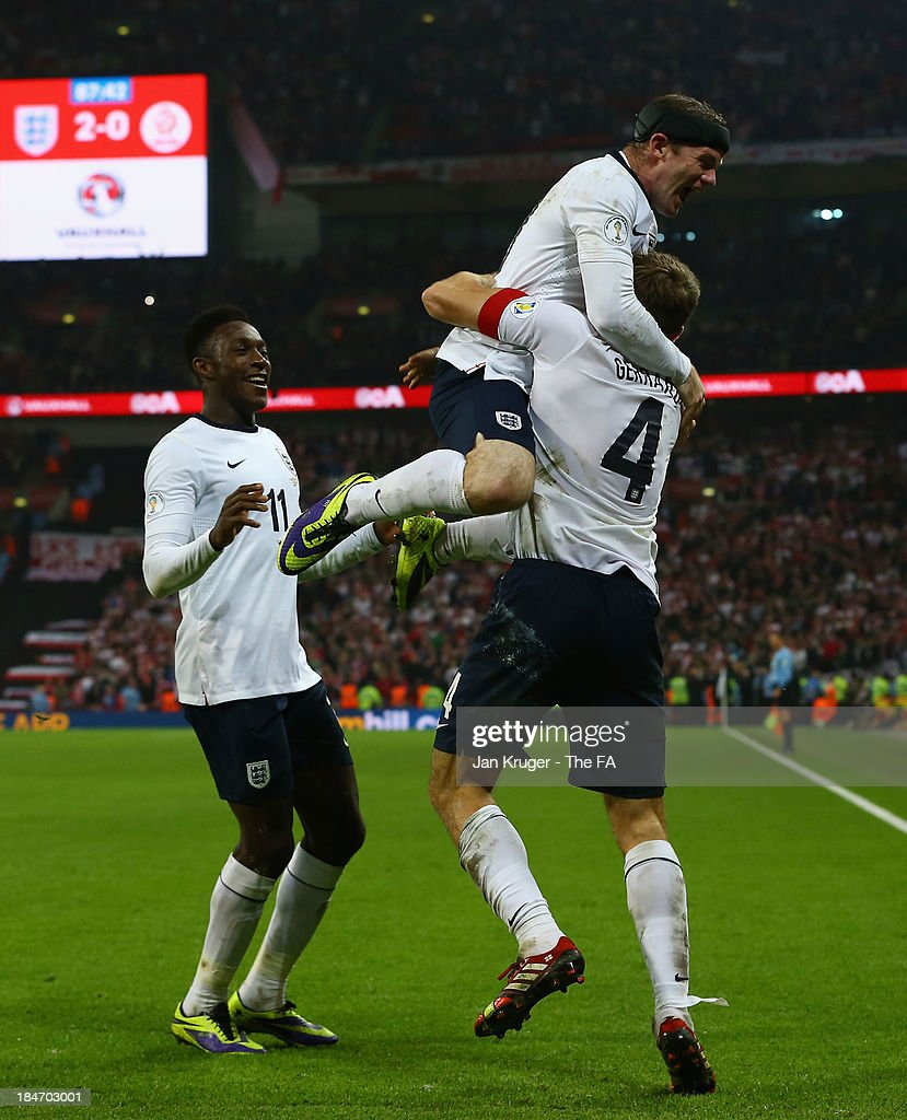 <a gi-track='captionPersonalityLinkClicked' href=/galleries/search?phrase=Steven+Gerrard&family=editorial&specificpeople=202052 ng-click='$event.stopPropagation()'>Steven Gerrard</a> celebrates scoring his goal with <a gi-track='captionPersonalityLinkClicked' href=/galleries/search?phrase=Wayne+Rooney&family=editorial&specificpeople=157598 ng-click='$event.stopPropagation()'>Wayne Rooney</a> and <a gi-track='captionPersonalityLinkClicked' href=/galleries/search?phrase=Danny+Welbeck&family=editorial&specificpeople=4223930 ng-click='$event.stopPropagation()'>Danny Welbeck</a> of England during the FIFA 2014 World Cup Qualifying Group H match between England and Poland at Wembley Stadium on October 15, 2013 in London, England.