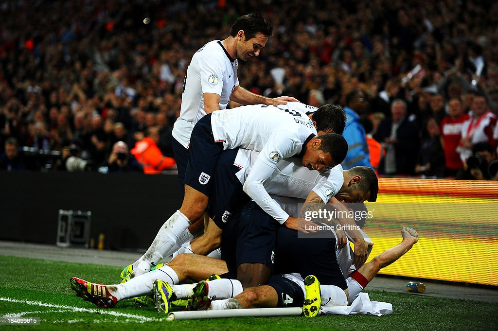 Steven Gerrard of England (obscured) celebrates with team mates as he scores their second goal during the FIFA 2014 World Cup Qualifying Group H match between England and Poland at Wembley Stadium on October 15, 2013 in London, England.