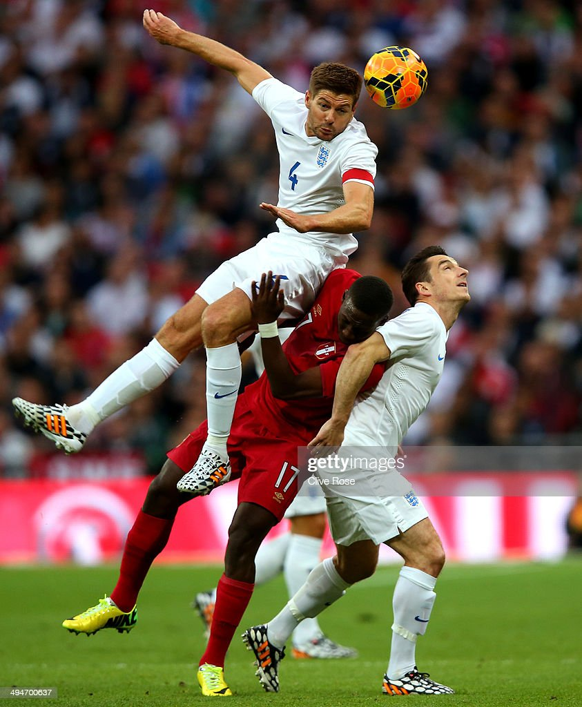 <a gi-track='captionPersonalityLinkClicked' href=/galleries/search?phrase=Steven+Gerrard&family=editorial&specificpeople=202052 ng-click='$event.stopPropagation()'>Steven Gerrard</a> of England cloimbs above Luis Advincula of Peru and <a gi-track='captionPersonalityLinkClicked' href=/galleries/search?phrase=Leighton+Baines&family=editorial&specificpeople=682452 ng-click='$event.stopPropagation()'>Leighton Baines</a> of England to win the ball during the international friendly match between England and Peru at Wembley Stadium on May 30, 2014 in London, England.