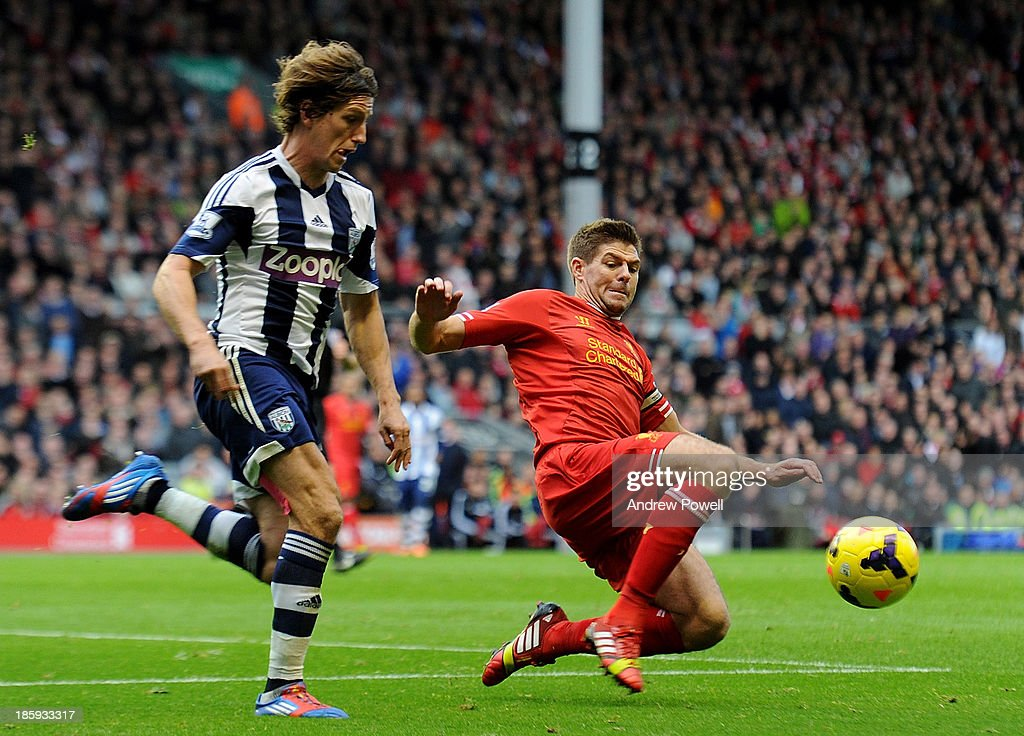 Steven Gerrard of Liverpool and Billy Jones of West Bromwich Albion compete during the Barclays Premier League match between Liverpool and West Bromwich Albion at Anfield on October 26, 2013 in Liverpool, England.