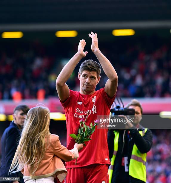 Steven Gerrard of Liverpool applauds the Kop end as his daughter brings him flowers after the Barclays Premier League match betrween Liverpool and...