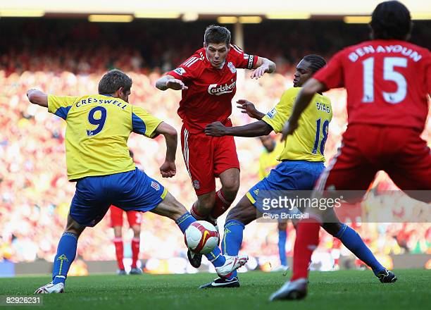 Steven Gerrard of Liverpool attempts to move between Richard Cresswell and Mamady Sidibe of Stoke City during the Barclays Premier League match...