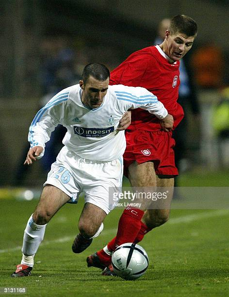 Steven Gerrard of Liverpool battles for the ball with Laurent Battles of Marseille during the UEFA Cup Fourth Round match between Marseille and...