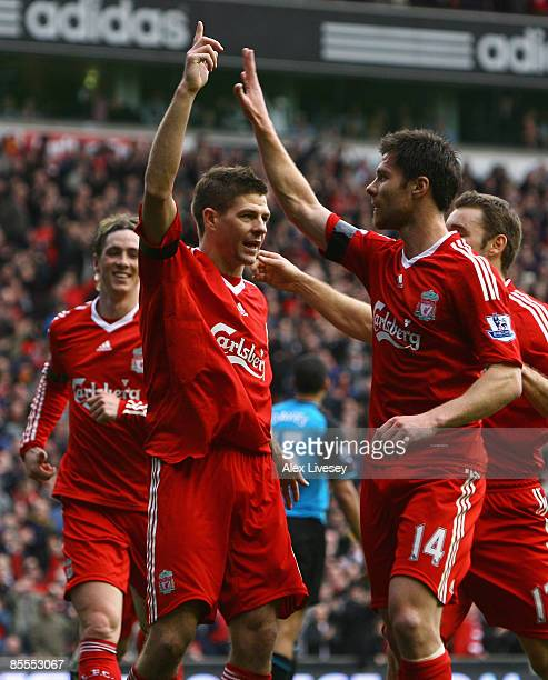 Steven Gerrard of Liverpool celebrates with his team mates after scoring his team's third goal during the Barclays Premier League match between...