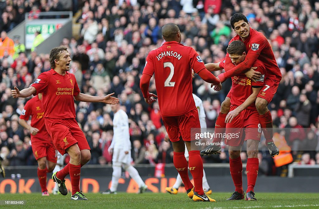 Steven Gerrard of Liverpool celebrates with Luis Suarez,Glen Johnson and Lucas after scoring the first goal from the penalty spot during the Barclays Premier League match between Liverpool and Swansea City at Anfield on February 17, 2013 in Liverpool, England.