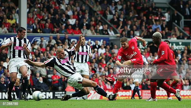 Steven Gerrard of Liverpool scores the opening goal in front of a lunging Darren Purse of West Brom during the FA Barclays Premiership match between...