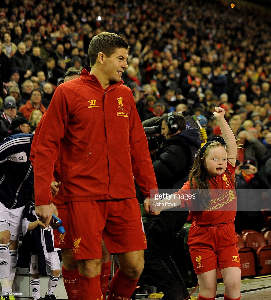 Steven Gerrard of Liverpool walks onto the pitch with tonights team mascot before the Barclays Premier League match between Liverpool and West Bromwich Albion at Anfield on February 11, 2013 in Liverpool, England.