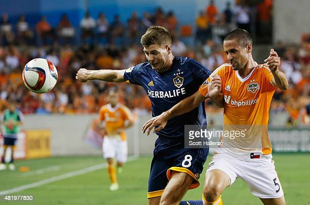 Steven Gerrard of the Los Angeles Galaxy battles for the ball with Raul Rodriguez of the Houston Dynamo at BBVA Compass Stadium on July 25 2015 in...