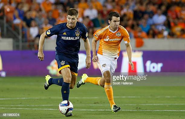 Steven Gerrard of the Los Angeles Galaxy battles for the ball with Nathan Sturgis of the Houston Dynamo at BBVA Compass Stadium on July 25 2015 in...