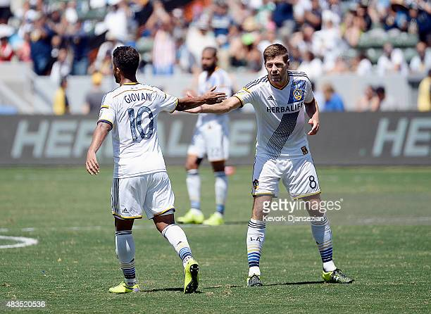 Steven Gerrard of the Los Angeles Galaxy congratulates Giovani Dos Santos as he walks off the pitch to be replaced against Seattle Sounders during...