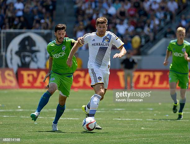 Steven Gerrard of the Los Angeles Galaxy drives the ball against Brad Evans of the Seattle Sounders during the first half at StubHub Center August 9...