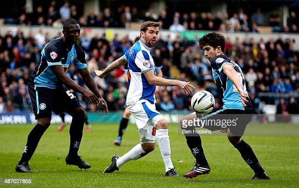 Steven Gillespie of Bristol passes under pressure from Anthony Stewart and Max Kretzschmar of Wycombe during the Sky Bet League Two match between...