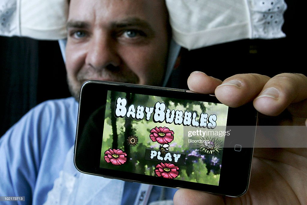 Steven 'Goody' Goodale displays an Apple iPhone loaded with 'Baby Bubbles,' a game he developed for iPhones, iPads, and the iPod Touch, during the Electronic Entertainment Expo (E3) in Los Angeles, California, U.S., on Wednesday, June 16, 2010. Sales of iPhone, iPod Touch and iPad, all of which can be used to play games, will reach 100 million units this month, Chief Executive Officer Steve Jobs said in May. Photographer: Jonathan Alcorn/Bloomberg via Getty Images