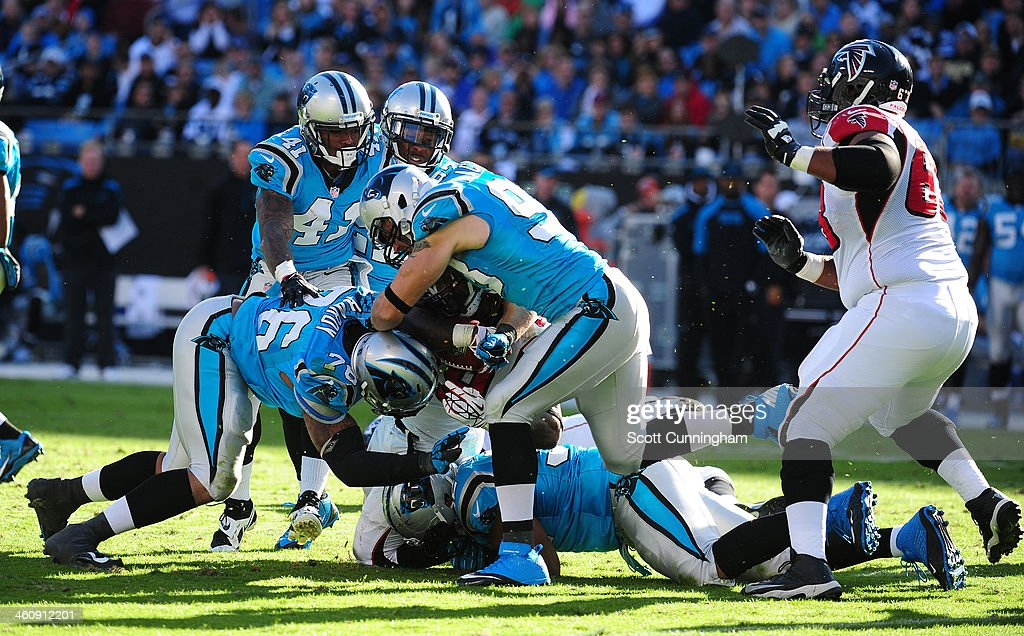 Steven Jackson of the Atlanta Falcons is tackled by Chase Blackburn Dwan Edwards and Greg Hardy of the Carolina Panthers at Bank of America Stadium...
