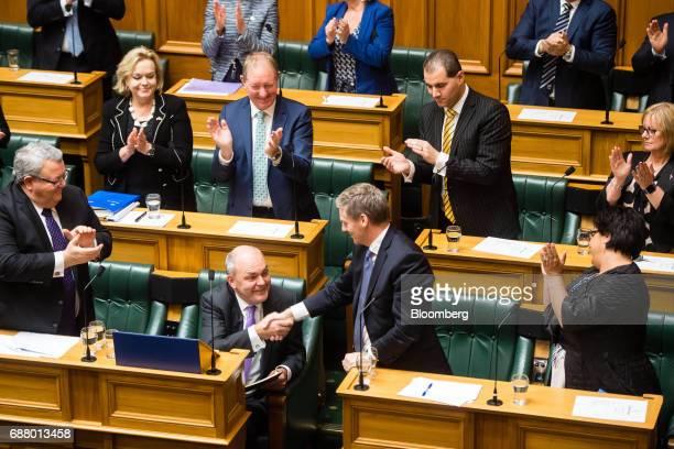 Steven Joyce New Zealand's finance minister bottom center left shakes hands Bill English prime minister bottom center right after delivering the...