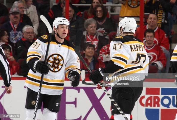 Steven Kampfer of the Boston Bruins skates over to congratulate teammate Marc Savard on a tipin goal during an NHL game against the Carolina...