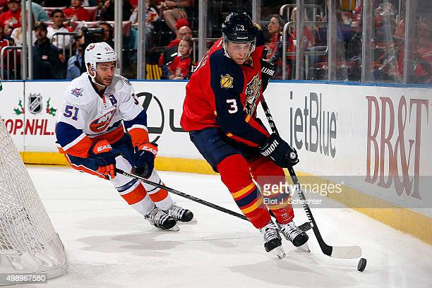 Steven Kampfer of the Florida Panthers skates with the puck against Frans Nielsen of the New York Islanders at the BBT Center on November 27 2015 in...