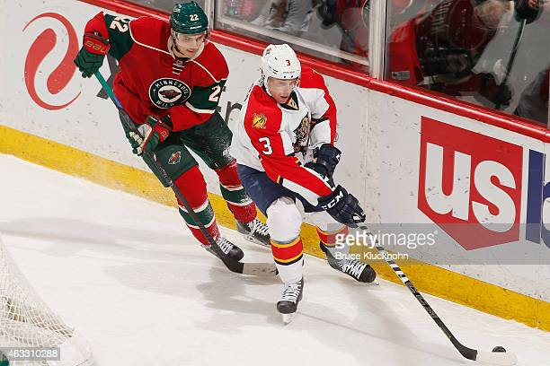 Steven Kampfer of the Florida Panthers skates with the puck while Nino Niederreiter of the Minnesota Wild defends during the game on February 12 2015...