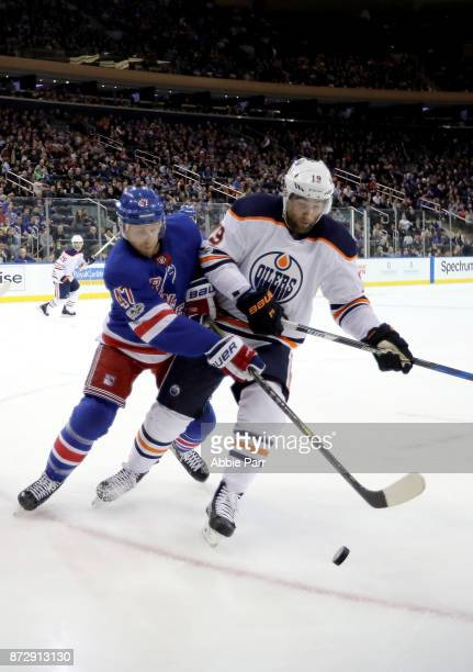 Steven Kampfer of the New York Rangers fights for the puck against Patrick Maroon of the Edmonton Oilers in the first period during their game at...