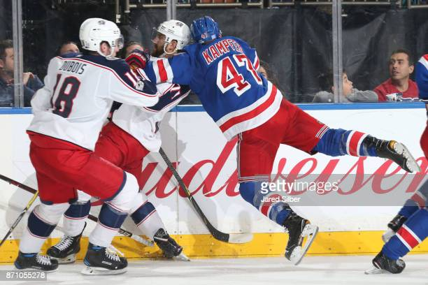 Steven Kampfer of the New York Rangers gets hit by Nick Foligno of the Columbus Blue Jackets at Madison Square Garden on November 6 2017 in New York...