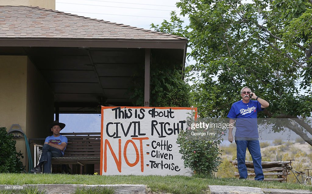 Steven Kelly (R) talks on a phone as he stands by a protest signs he posted on his house as his soon Sean Kelly (L), looks on, along U.S. 170 on April 11, 2014 west of Mesquite, Nevada. Bureau of Land Management officials are rounding up Cliven Bundy's cattle, he has been locked in a dispute with the BLM for a couple of decades over grazing rights. (Photo by George Frey/Getty Images