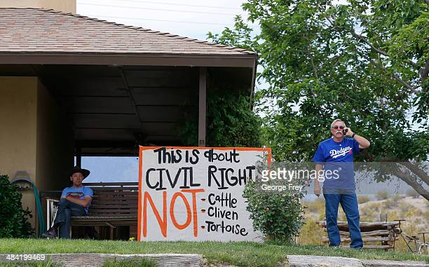 Steven Kelly talks on a phone as he stands by a protest signs he posted on his house as his soon Sean Kelly looks on along US 170 on April 11 2014...