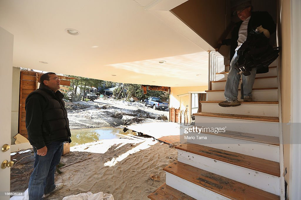 Steven Lawit (R) and David Oppenheim recover items from Lawit's destroyed home on November 21, 2012 in Mantoloking, New Jersey. Mantoloking was one of the hardest hit areas by Superstorm Sandy.
