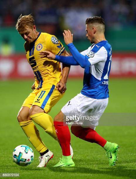 Steven Lewerenz of Kiel and Jan Hochscheidt of Braunschweig battle for the ball during the DFB Cup first round match between Holstein Kiel and...