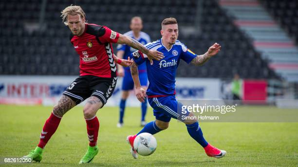Steven Lewerenz of Kiel is challenged by Kai Gehring of Grossaspach during the 3 Liga match between Sonnenhof Grossaspach and Holstein Kiel at...