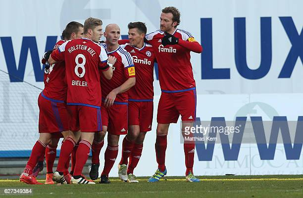 Steven Lewerenz of Kiel jubilates with team mates after scoring the second goal during the third league match between FC Hansa Rostock and Holstein...