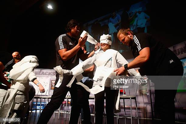 Steven Luatua and Joe Moody of the All Blacks dress a young fan in toilet paper to design a wedding dress during a New Zealand All Blacks community...