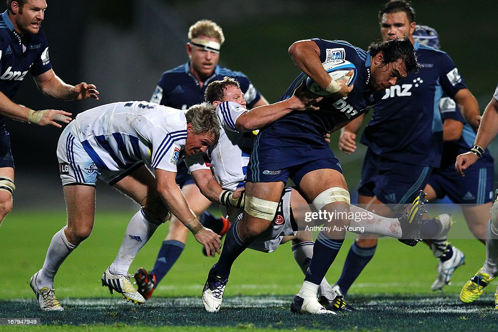 Steven Luatua of the Blues charges on despite the tackle from <a gi-track='captionPersonalityLinkClicked' href=/galleries/search?phrase=Jean+de+Villiers&family=editorial&specificpeople=2285701 ng-click='$event.stopPropagation()'>Jean de Villiers</a> and Deon Fourie of the Stormers during the round 12 Super Rugby match between the Blues and the Stormers at North Harbour Stadium on May 3, 2013 in Auckland, New Zealand.