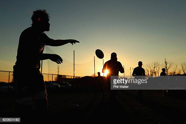 Steven Luatua of the New Zealand All Blacks passes to Charlie Faumuina as the sun sets during a training session at Toyota Park on November 3 2016 in...
