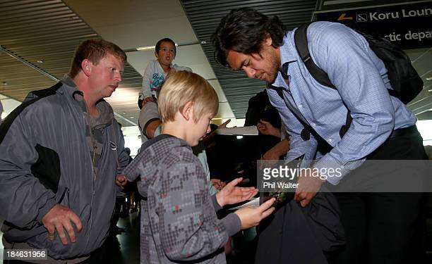 Steven Luatua of the New Zealand All Blacks signs autographs as the team arrives at the Dunedin International Airport on October 15 2013 in Dunedin...