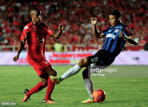 Steven Lucumi of America vies for the ball with Alexis Perez of Atletico Junior during a match between America de Cali and Atletico Junior as part of...