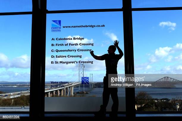 Steven Marshall puts up logos on a window displaying the shortlist of names for the new Forth Replacement Crossing at the Education Centre South...