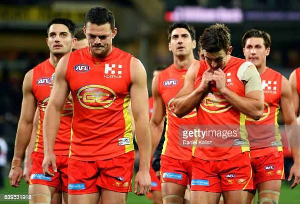 Steven May and Jarryd Lyons of the Suns walk from the field looking dejected after being defeated by the Power during the round 23 AFL match between...