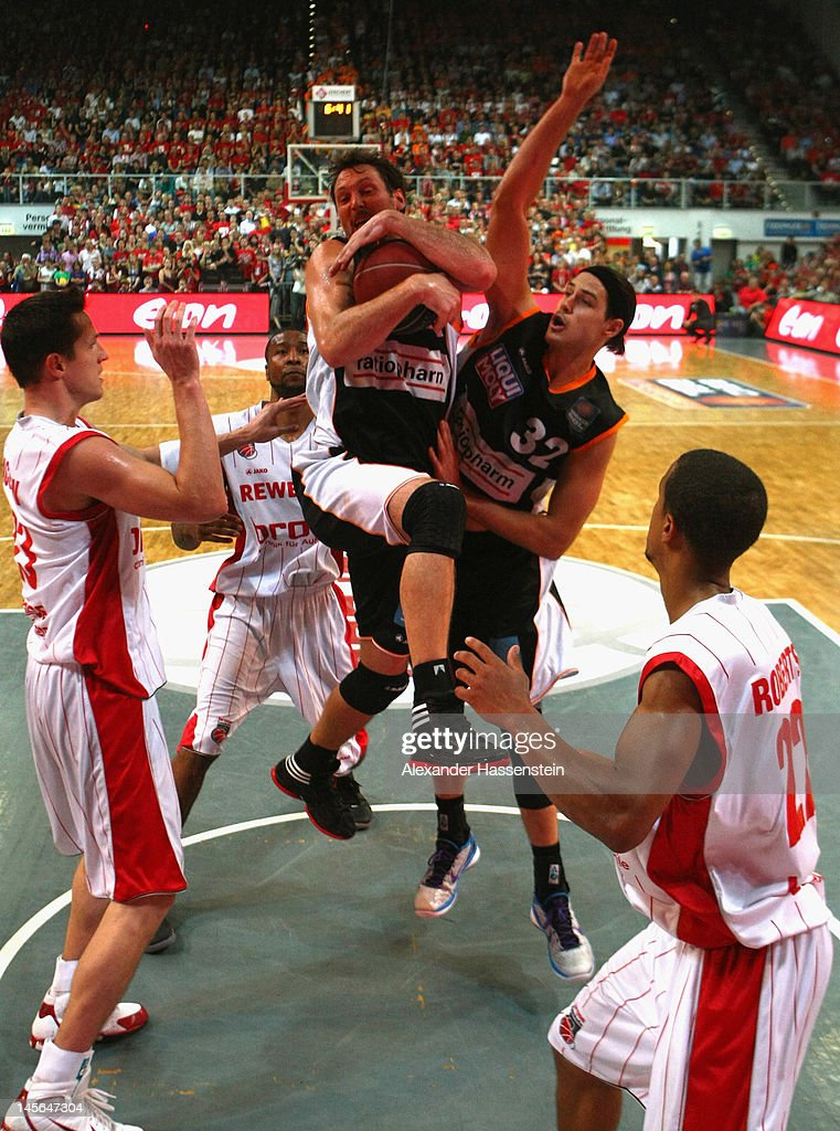 Steven Michael Esterkamp (C-L) of Ulm and his team mate Dane Watts (C-R) battle for the ball with Casey Jacobsen (L) of Bamberg and his team mate Brian Roberts (R) during game 1 of the Beko BBL finals between Brose Baskets and ratiopharm Ulm at Stechert Arena on June 3, 2012 in Bamberg, Germany.