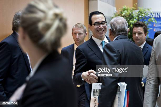 Steven Mnuchin US Treasury secretary center greets an attendee while walking to a Group of 20 finance ministers and central bank governors meeting on...