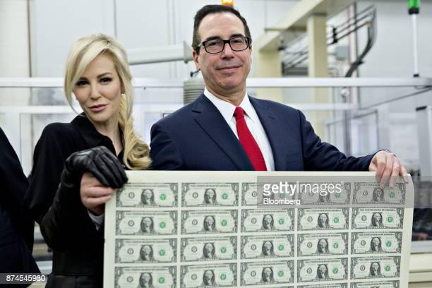 Steven Mnuchin US Treasury secretary right and his wife Louise Linton hold a 2017 50 subject uncut sheet of $1 dollar notes bearing Mnuchin's name...