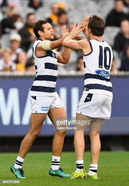 Steven Motlop of the Cats is congratulated by Daniel Menzel after kicking a goal during the round four AFL match between the Hawthorn Hawks and the...