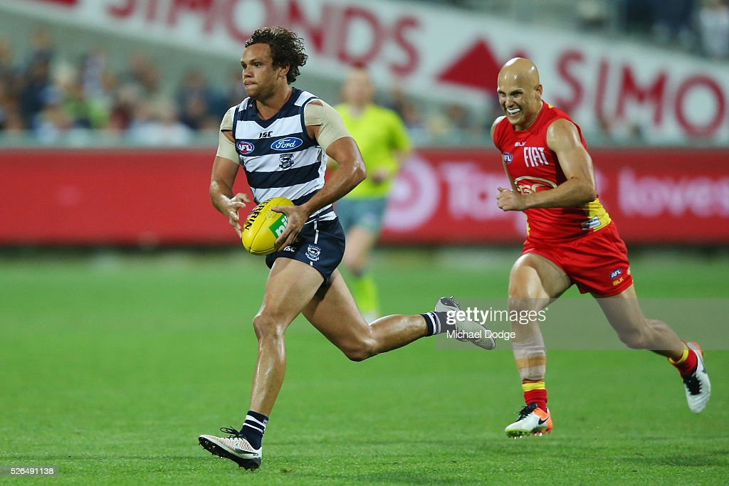 Steven Motlop of the Cats runs with the ball away from <a gi-track='captionPersonalityLinkClicked' href=/galleries/search?phrase=Gary+Ablett&family=editorial&specificpeople=206196 ng-click='$event.stopPropagation()'>Gary Ablett</a> of the Suns during the round six AFL match between the Geelong Cats and the Gold Coast Suns at Simonds Stadium on April 30, 2016 in Geelong, Australia.