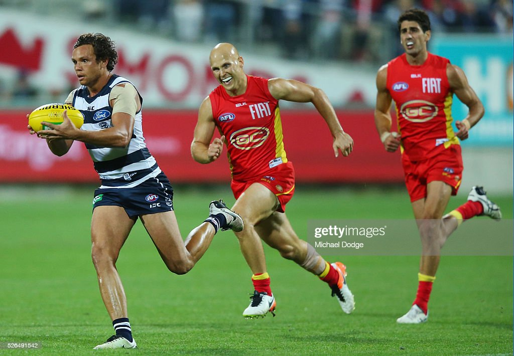 Steven Motlop of the Cats runs with the ball away from Gary Ablett of the Suns during the round six AFL match between the Geelong Cats and the Gold Coast Suns at Simonds Stadium on April 30, 2016 in Geelong, Australia.