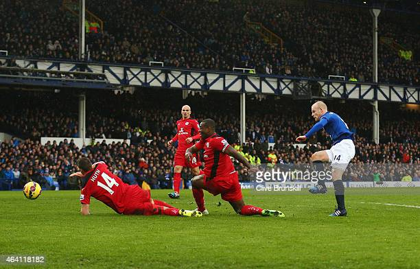 Steven Naismith of Everton shoots past Wes Morgan and Robert Huth of Leicester City to score their first goal during the Barclays Premier League...