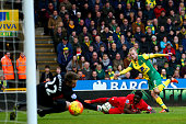 Steven Naismith of Norwich City scores his team's second goal past Simon Mignolet of Liverpool during the Barclays Premier League match between...