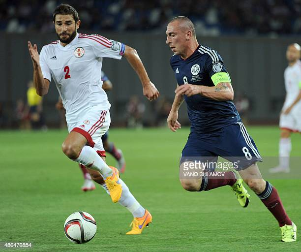 Steven Naismith of Scotland vies for a ball with Solomon Kverkvelia of Georgia during their Euro 2016 qualifying football match between Georgia and...