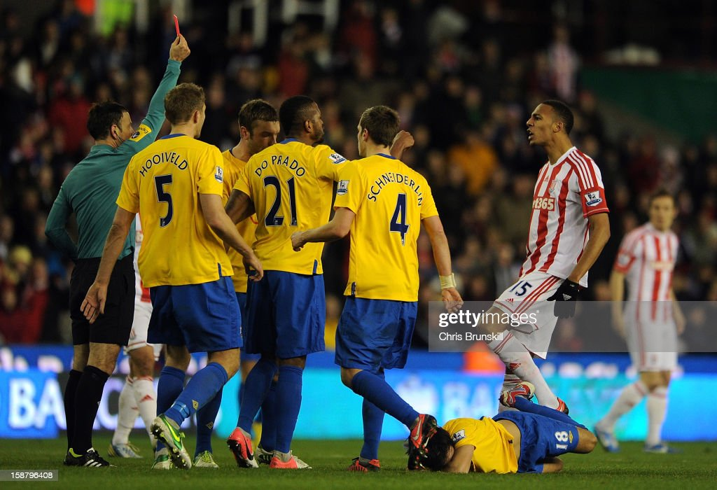 Steven Nzonzi (R) of Stoke City is sent-off by referee <a gi-track='captionPersonalityLinkClicked' href=/galleries/search?phrase=Mark+Clattenburg&family=editorial&specificpeople=2108870 ng-click='$event.stopPropagation()'>Mark Clattenburg</a> (L) for fouling Jack Cork of Southampton, who lies injured on the floor during the Barclays Premier League match between Stoke City and Southampton at Britannia Stadium on December 29, 2012 in Stoke on Trent, England.