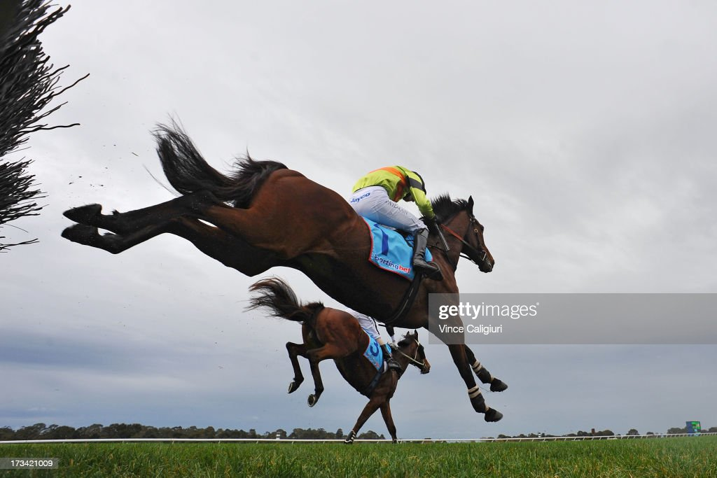 Steven Pateman riding Bashboy (front) jumps the steeple and goes on to win the Crisp Steeplechase from Brad McLean riding Cats Fun (3)) during the Grand National Hurdle Day at Sportingbet Park on July 14, 2013 in Melbourne, Australia.